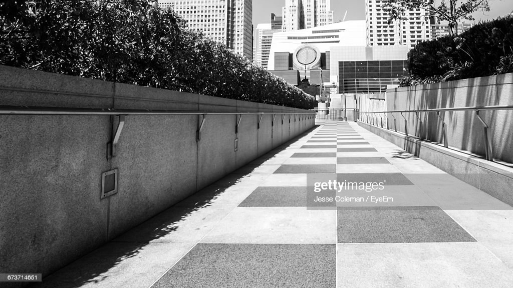 Empty Footpath Leading Towards Buildings On Sunny Day : Stock Photo