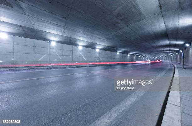 Empty freeway headed into a lighted road tunnel