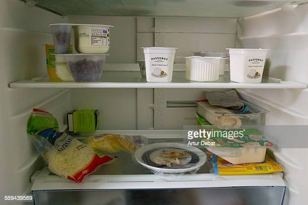 Empty fridge with low products on home kitchen