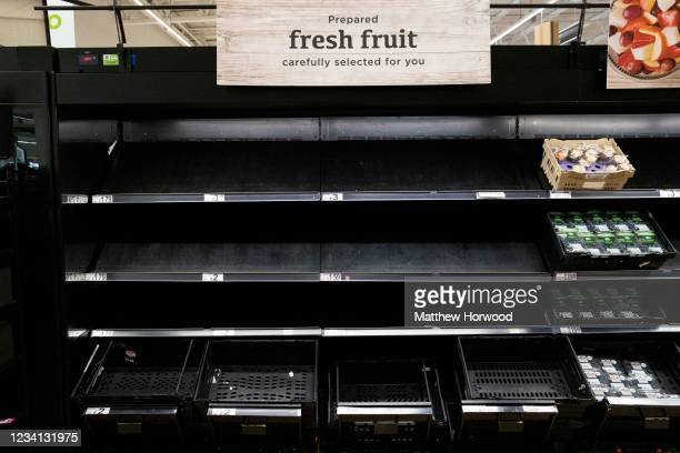 Empty fruit and veg shelves in an ASDA store on July 23, 2021 in Cardiff, United Kingdom. Supermarkets across the UK are emptying of fresh produce...