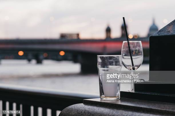 empty glasses left outside in london, uk, city on the background, selective focus. - empty glasses after party stock pictures, royalty-free photos & images