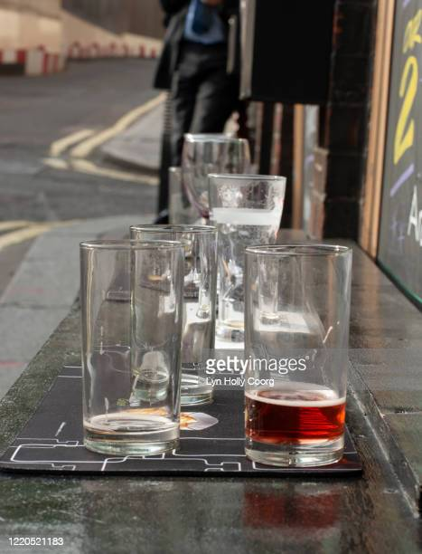 empty glasses on a table outside a pub bar - lyn holly coorg stock pictures, royalty-free photos & images