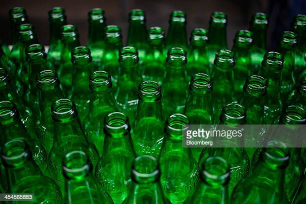 Empty green glass bottles travel down a conveyor belt before being labeled washed and filled with gingerflavored soft drink at the Ale8One Bottling...