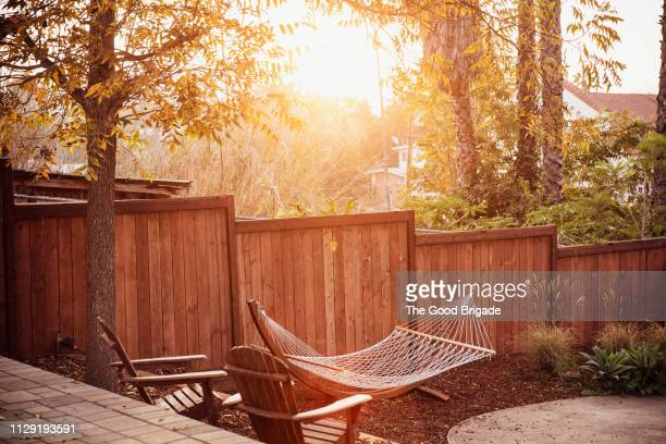 empty hammock hanging in backyard - fence stock pictures, royalty-free photos & images