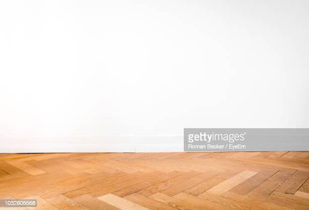 empty hardwood floor against white wall at home - wooden floor stock pictures, royalty-free photos & images