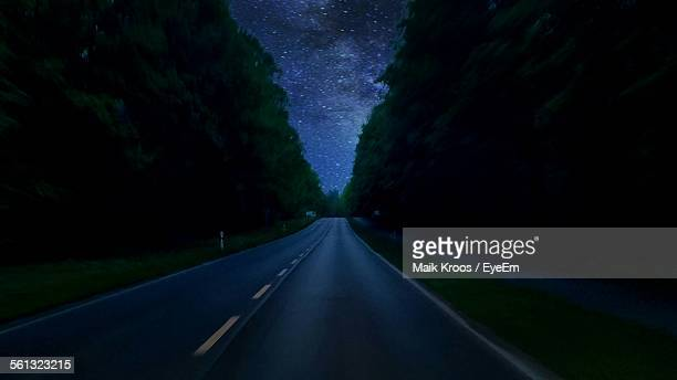 Empty Highway Amidst Trees At Night