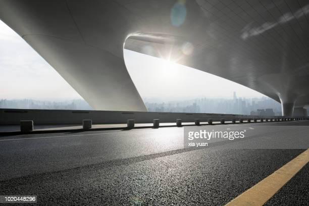 empty highway with futuristic architecture - städtischer verkehrsweg stock-fotos und bilder