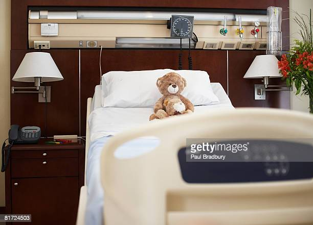 Empty hospital bed with teddy bear on it