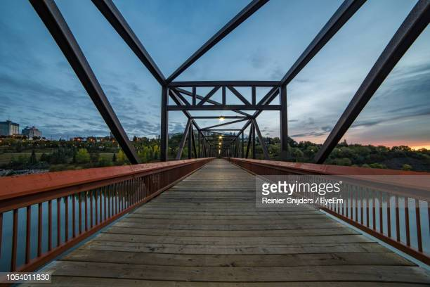 empty illuminated footbridge on river against sky during sunset - edmonton stock pictures, royalty-free photos & images