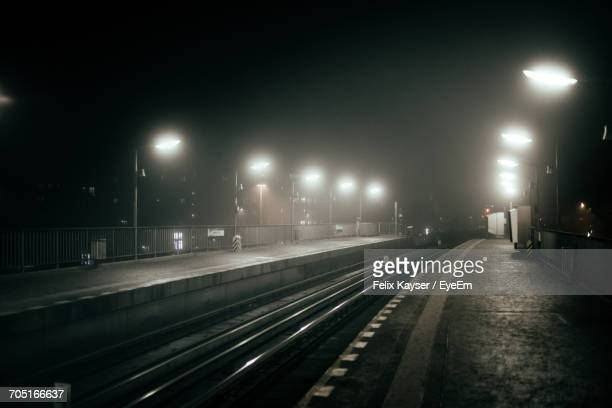 Empty Illuminated Railroad Station At Night During Foggy Weather