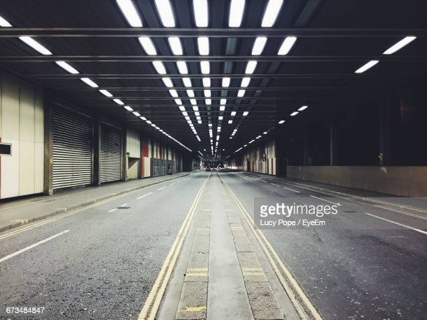 empty illuminated road amidst shops - diminishing perspective stock pictures, royalty-free photos & images