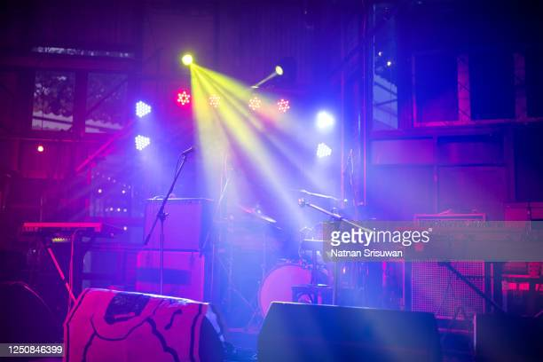 empty illuminated stage with drum kit, guitar and microphones. - film festival stock pictures, royalty-free photos & images
