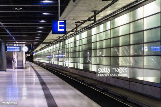 empty illuminated subway station - bahnhof stock-fotos und bilder