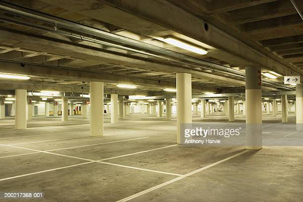 empty illuminated underground carpark - parking garage stock pictures, royalty-free photos & images