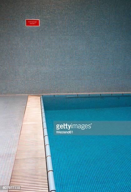 Empty indoor swimming pool with sign at the wall