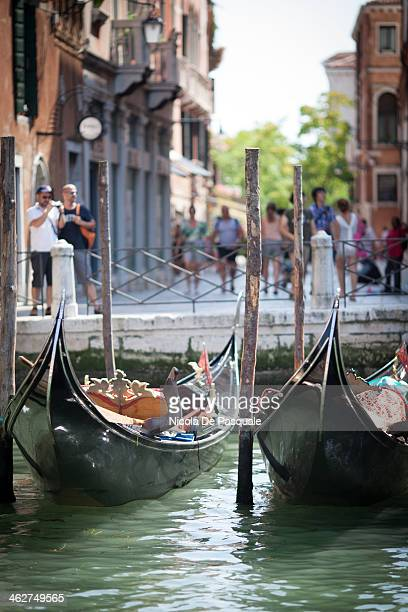 CONTENT] Empty Italian gondolas moored on Grand Canal Some tourists taking pictures and discovering the city on background Venice July 15 2013