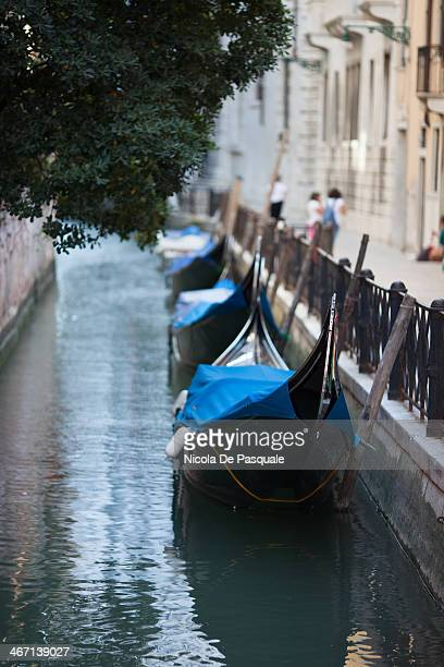 CONTENT] Empty Italian gondolas moored on narrow canal of Venice Some apartment buildings on sides