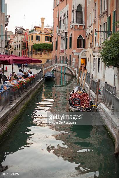 CONTENT] Empty Italian gondolas moored on narrow street of Venice Some colored apartment and tourists sitted and eating at Italian restaurants on...