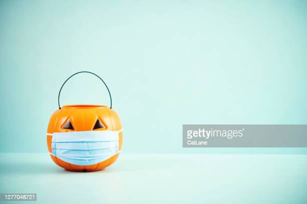 empty jack o'lantern trick or treat bucket with face mask halloween background - halloween wallpaper stock pictures, royalty-free photos & images