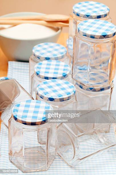 Empty jam jars on tea towel; sugar