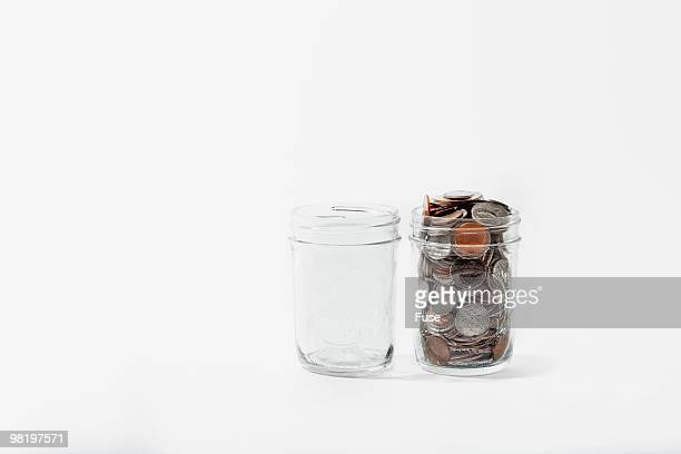 Empty jar beside jar filled with coins
