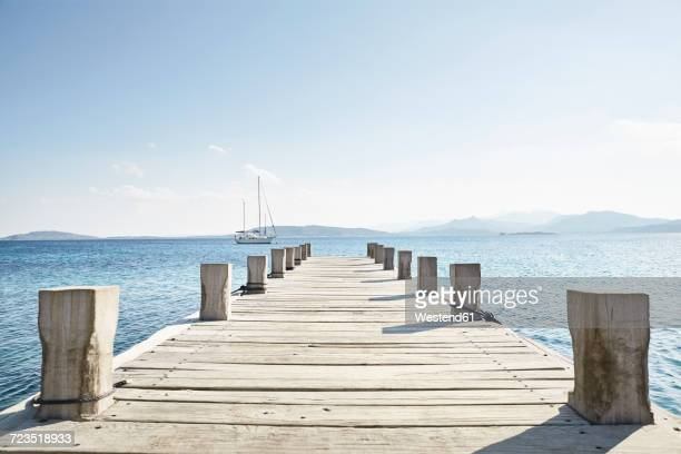 empty jetty and saling boat in the background - jetty stock pictures, royalty-free photos & images