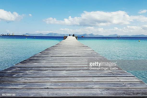 Empty Jetty Leading To Sea Against Sky