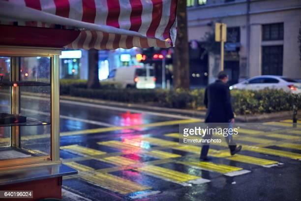 empty kiosk and pedestrian crossing on a rainy night. - emreturanphoto stock-fotos und bilder