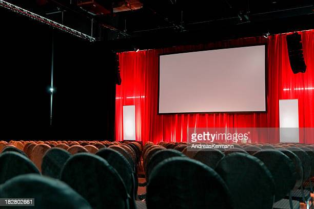 Empty large auditorium with a red curtain and blank screen