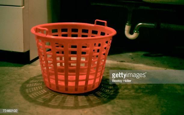 Empty laundry basket on floor in basement