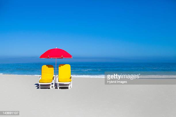 empty lawn chairs and umbrella on beach - sombrilla de playa fotografías e imágenes de stock