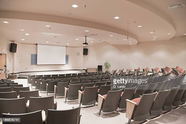 empty lecture hall with several rows of seats and a screen - auditorium stock pictures, royalty-free photos & images