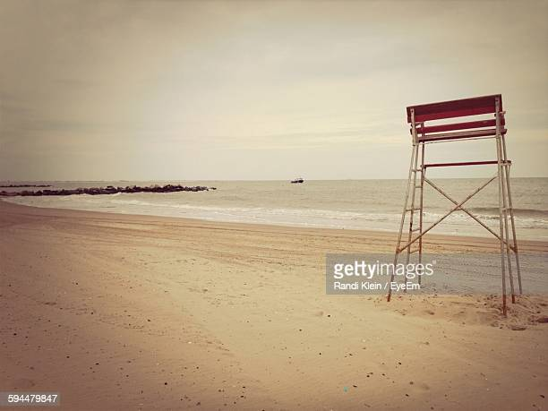 Empty Lifeguard Tower On Beach Against Sky