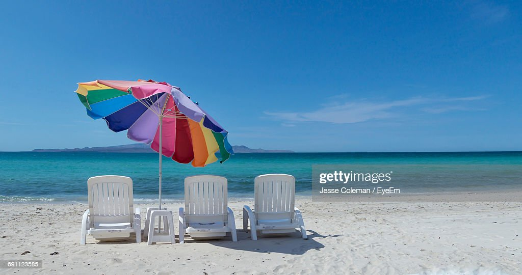 Empty Lounge Chairs And Umbrella At Beach Against Blue Sky : Foto de stock