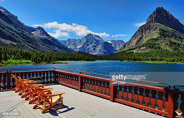 Empty lounge chairs beckon the traveler to sit and view the massive mountains in Glacier National Park in northern Montana, USA