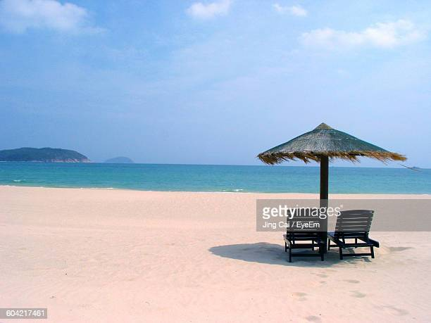 Empty Lounge Chairs With Parasol On Sandy Beach Against Sky