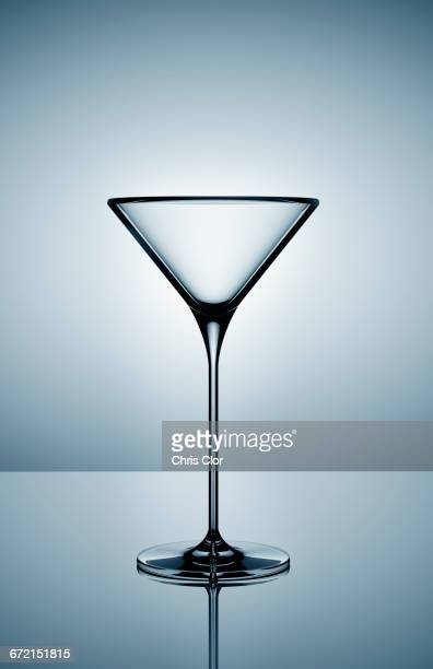 Empty martini glass on gray background