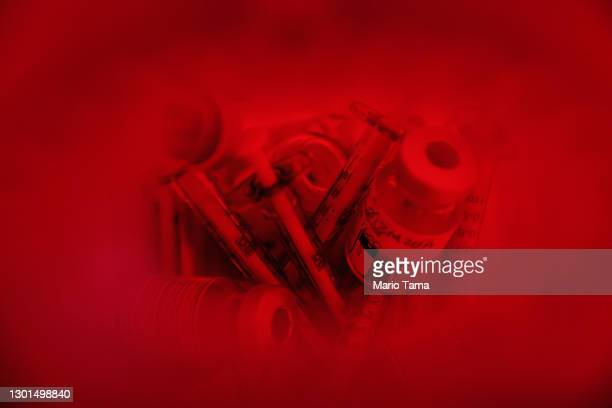 Empty Moderna COVID-19 vaccine vials and syringes rest in a medical waste container after being used at a vaccination clinic at the Los Angeles...