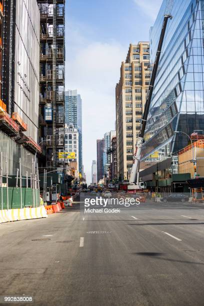 empty new york city street with skyscraper construction - midtown manhattan stock pictures, royalty-free photos & images