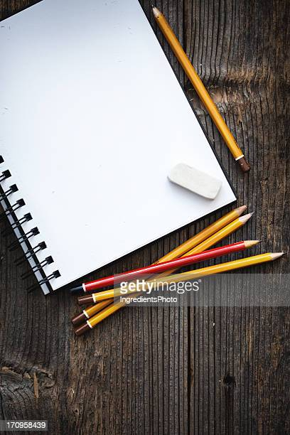 Empty notepad with five pencils and eraser on wooden table.