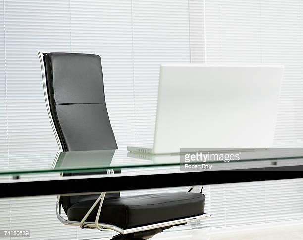 空のオフィスチェア付きのデスクにノートパソコン