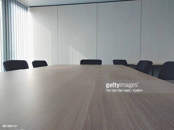 empty office chairs by table in conference room - tavolo da conferenza foto e immagini stock