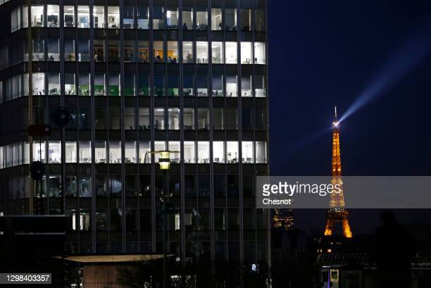 Empty office spaces are illuminated in skyscrapers at night after the 6 pm city-wide night time curfew in the La Defense business district during the...