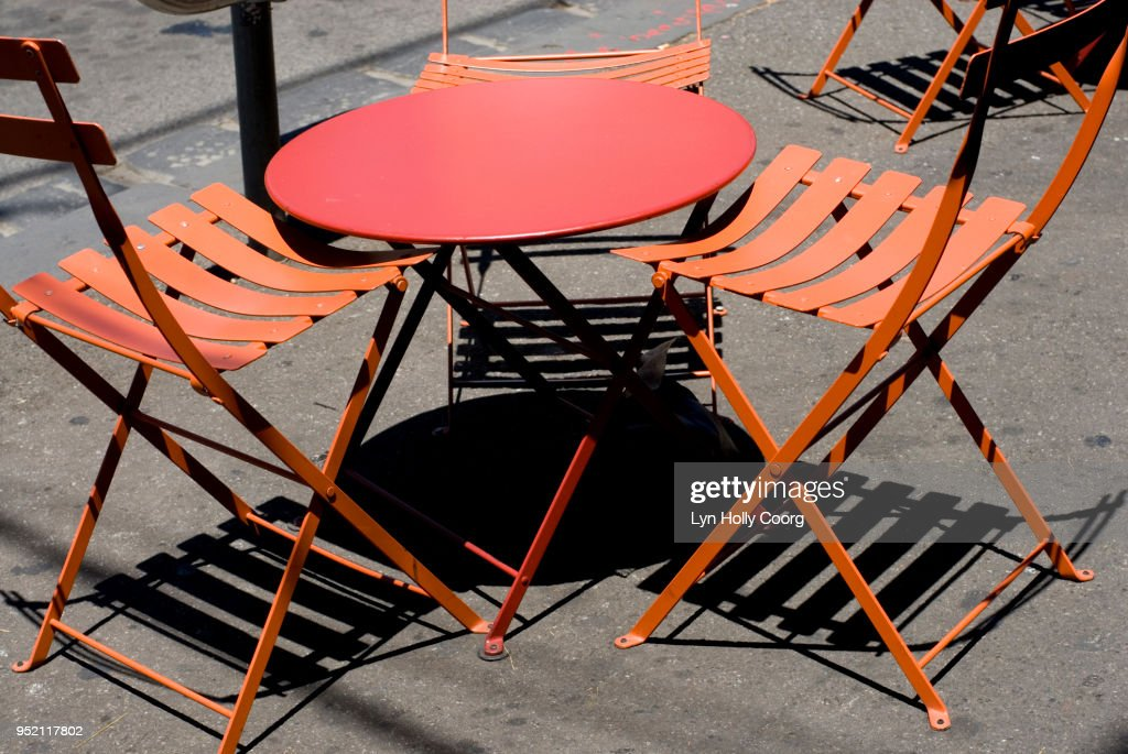 Empty Orange cafe table and chairs with shadows : Stock Photo