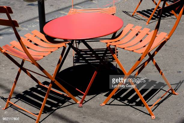 empty orange cafe table and chairs with shadows - lyn holly coorg stock-fotos und bilder