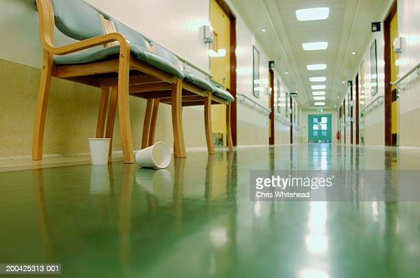 Empty paper cups by row of chairs in hospital corridor, ground view
