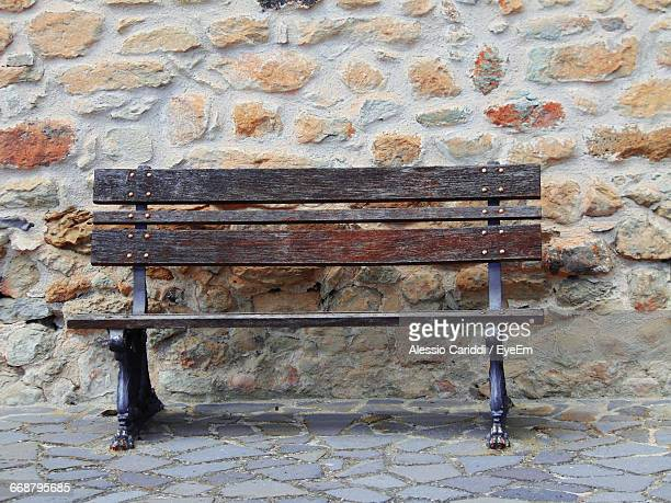 Empty Park Bench Against Stone Wall