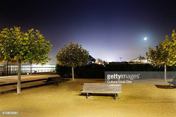 Empty park bench by river at night