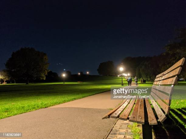 empty park bench by street against sky at night - night stock pictures, royalty-free photos & images