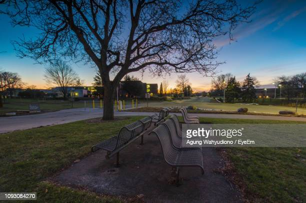 empty park bench on field against sky during sunset - kalamazoo stock pictures, royalty-free photos & images